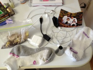 A family picture from 5 years ago, two iPhone cords, earbuds, some other random cord, a Fitbit that doesn't work, two mis-matched socks (??), a bag of crumbled up cookies, and an icing tip. Because you never know when you're going to have a cupcake decorating emergency.